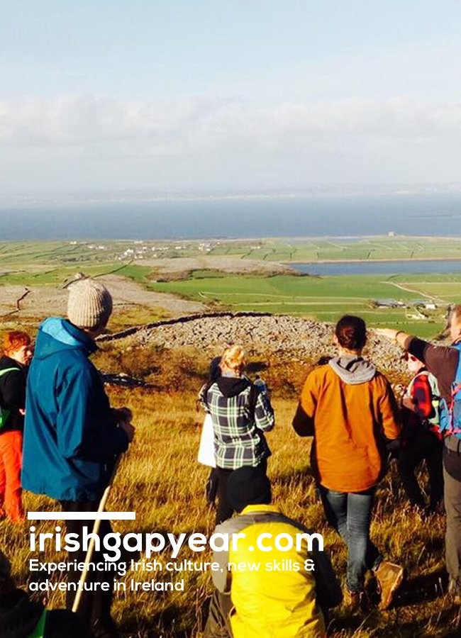 Young people stood on hill looking out towards sea in Ireland