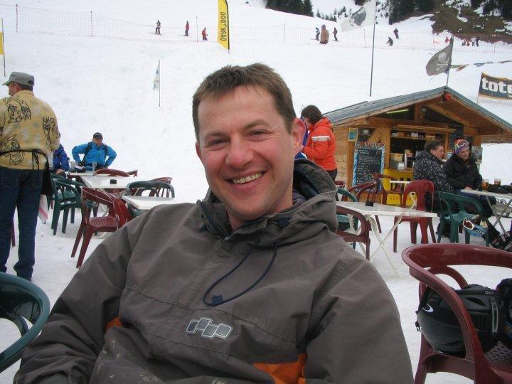 Jon Lomax smiling for camera sitting outside in ski resort France