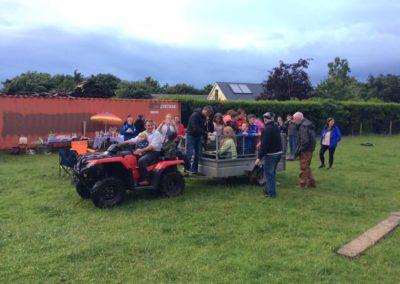 Children in trailer being towed in field Ballintrillick