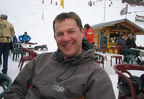 Jon Lomax smiling for camera sitting outside in ski resort France