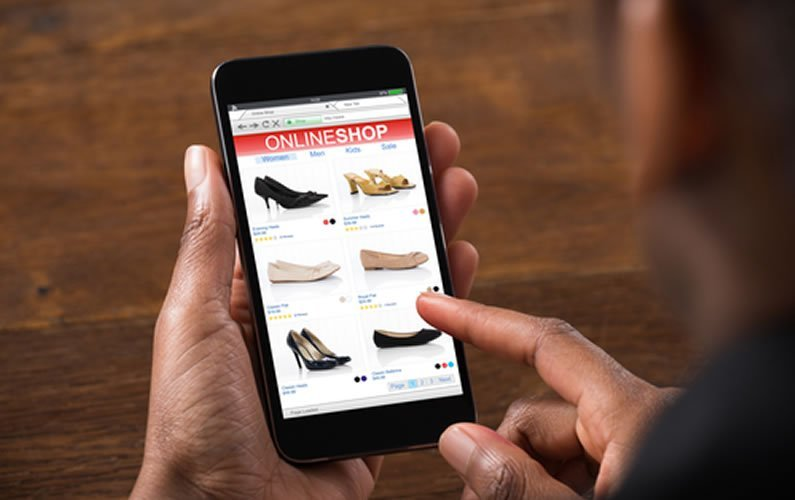 Man looking at shoes to buy online on his mobile phone