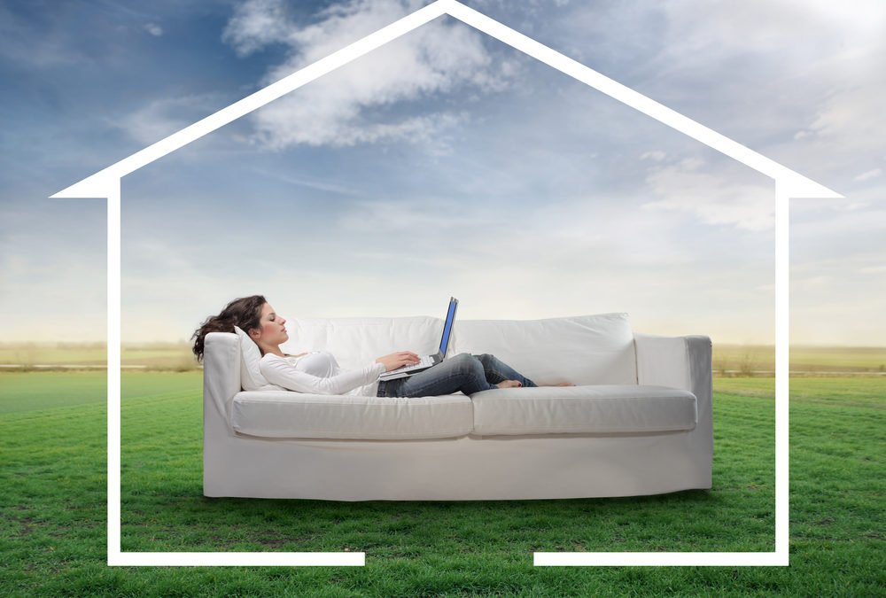 Woman on sofa in field with house around her